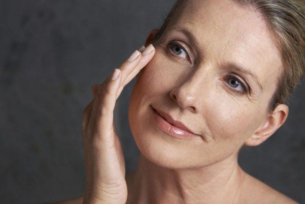 Женщина среднего возраста трогает кончиками пальцев одной руки лицо, наклонив голову набок