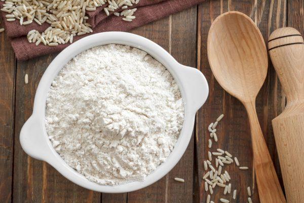 Чашка с рисовой мукой стоит на деревянном столе, усыпанном рисовыми зёрнами, рядом с ложкой и скалкой
