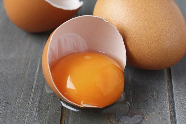 Яичный желток в скорлупе на фоне двух яиц лежит на деревянном сером столе