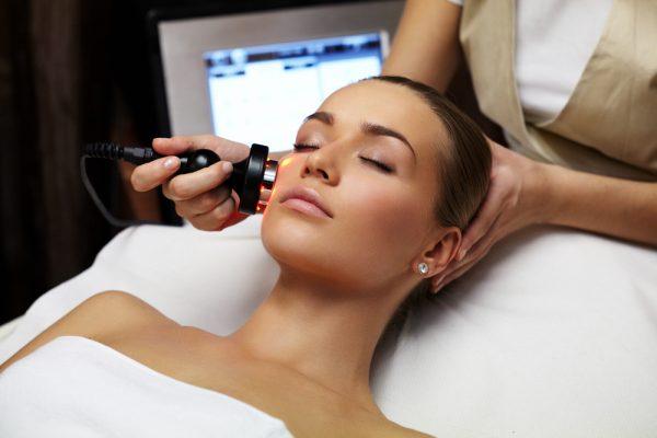 Косметолог воздействует аппаратом на кожу пациентки