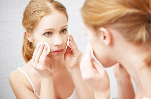 Отражение в зеркале девушки, приложившей к щекам ватные диски