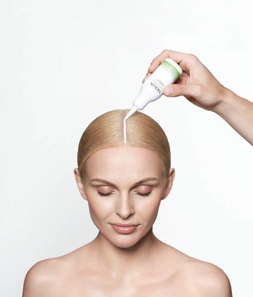 Женщине делают пилинг кожи головы