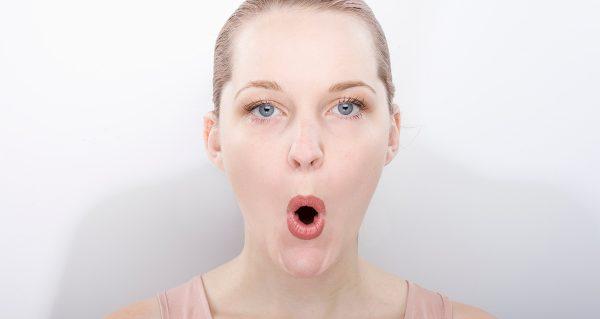 Девушка вытягивает губы в форме овала