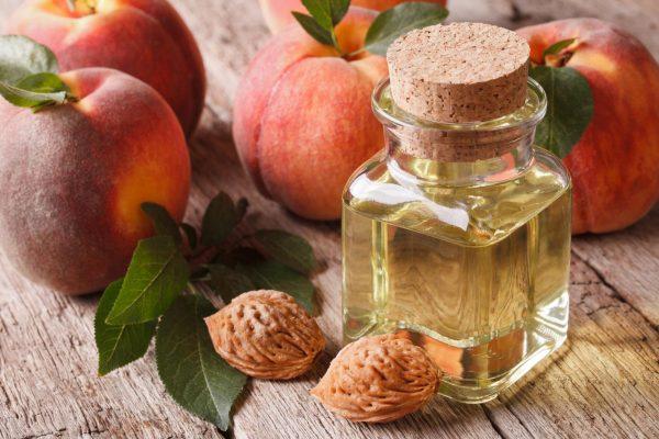 Персиковое масло в стеклянной бутылочке и персики