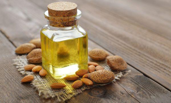 Миндальное масло в стеклянной бутылочке на столе