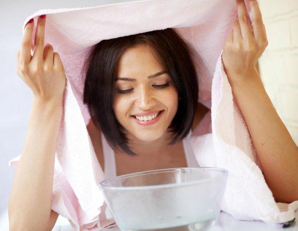 Девушка держит лицо над паровой ванночкой