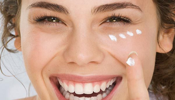 Девушка наносит крем вокруг глаз