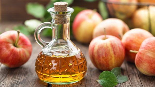 Яблочный уксус в прозрачной ёмкости и яблоки