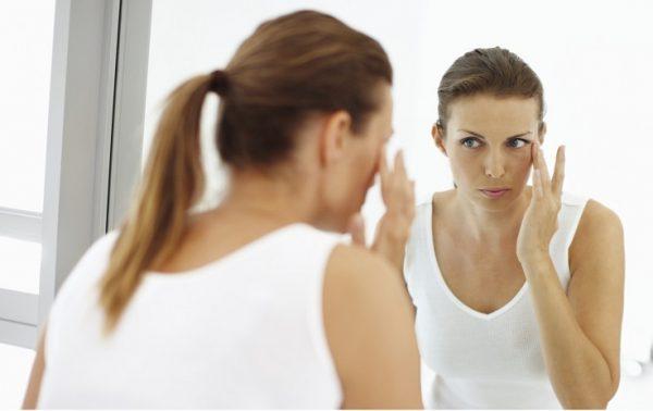 Нанесение женщиной ухаживающего крема на лицо